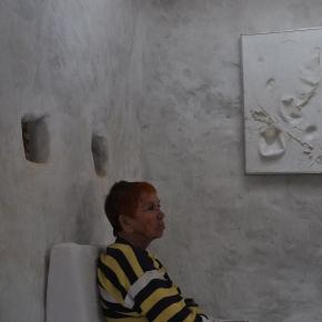 Isabel dans la salle blanche de Formentera avec au mur un relief tactile polymère des années 70